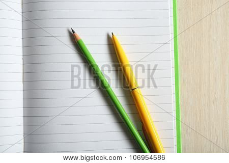 Opened striped note book with stationery on wooden background, close up