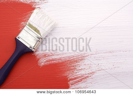 Paintbrush With White Paint Painting Over Red