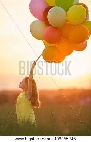 Beautiful girl with balloons in the field