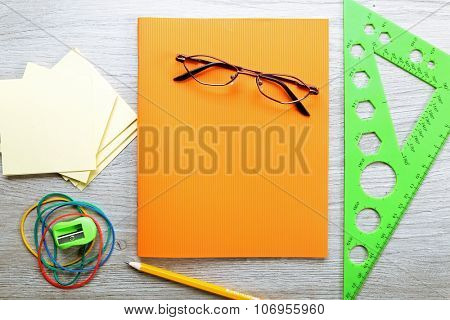 Colourful stationery on grey wooden background, close up