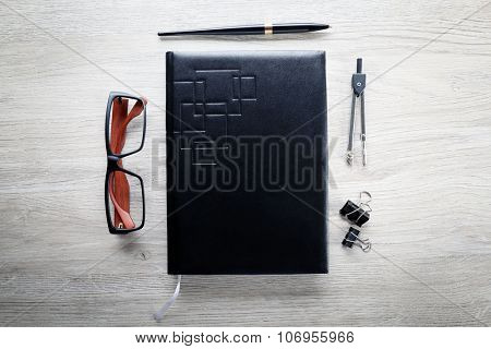 Workplace - black notebook and stationery on grey wooden background