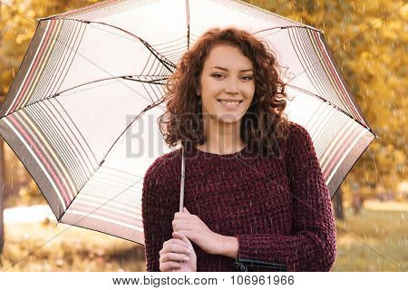 Young woman with umbrella at autumn rainy day