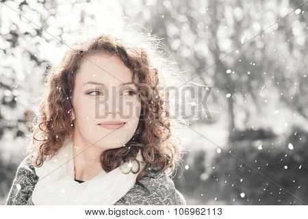 Outdoors portrait of a young beautiful woman with falling snow