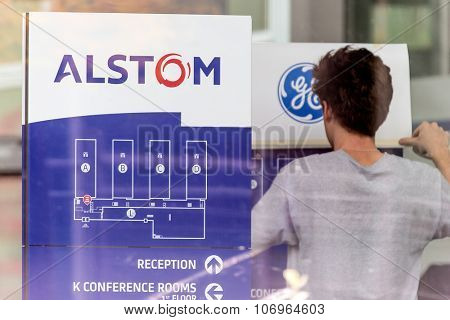 BADEN, SWITZERLAND. October 31st, 2015. Alstom logos being removed by worker to install GE logos before merger and acquisition of General Electric on 2nd November 2015.
