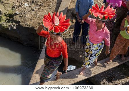 MANDALAY, MYANMAR, JANUARY 21, 2015 : Burmese women are boarding a boat by walking on a wooden plank, carrying watermelon slices on their heads  in Mandalay, Myanmar (Burma)