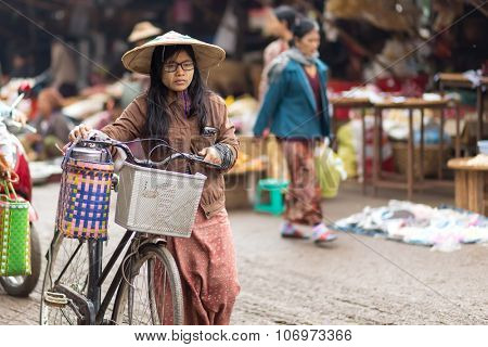 MANDALAY,MYANMAR,JANUARY 17, 2015 : A woman is walking, using his bicycle to carry some stuffs in the muddy street of the Zegyo outdoors market, in Mandalay, Myanmar (Burma).