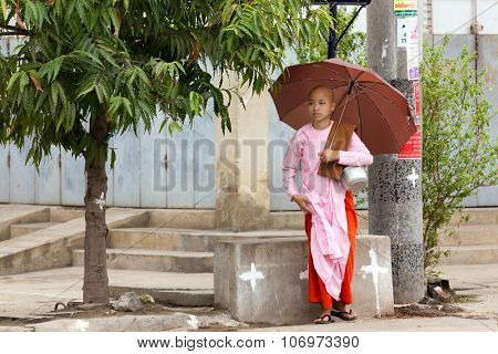 MANDALAY,MYANMAR,JANUARY 17, 2015 : A young Buddhist nuns is standing with her umbrella in the streets of Mandalay, Myanmar (Burma).