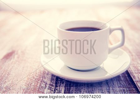 coffee of espresso in a white cup isolated on a wooden background