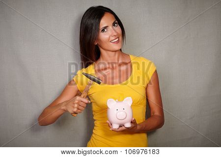 Good-looking Lady Breaking Piggy Bank With Hammer