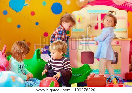 Cute Little Kids Playing With Toys In Nursery Group Of Kindergarten
