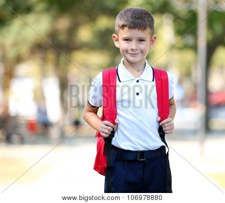 Little boy with large school bag, outdoor