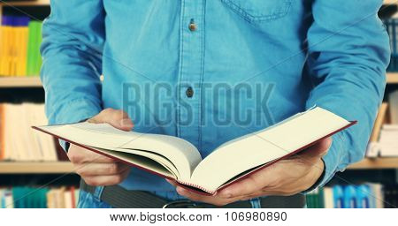 Male hands holding open book on bookshelves background