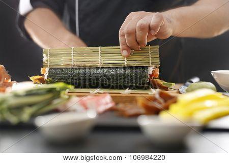 Sushi master prepares futomaki