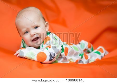 Baby Girl Lying On A Belly On An Orange Pillow