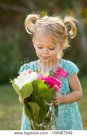 Adorable little girl holding a bouquet of flowers outside