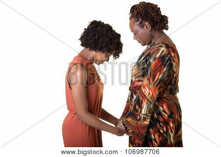 A mother and daughter praying