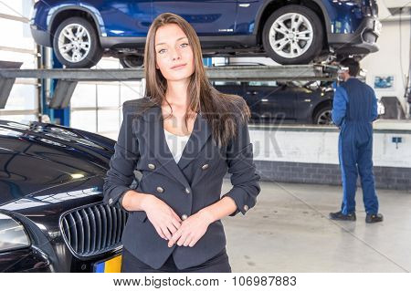 A pleased customer, posing in front of her justly fixed car at a high end garage, with a mechanic tending to another vehicle in the background