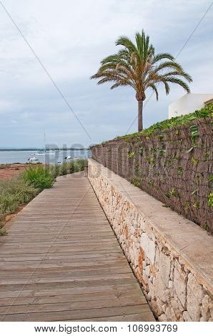 Wood boardwalk outside residential straw and stone fence