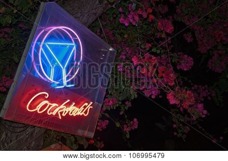 Pink bougainvillea and bright cocktail bar neon sign