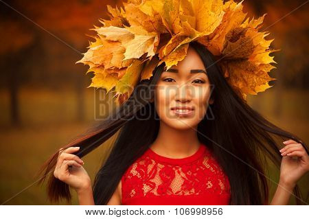 Asian woman with wreath of maple leaves