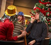 image of nuclear family  - Happy family of three celebrating in new year eve hat at home - JPG