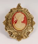 stock photo of cameos  - antique gold cameo with ladies face over on white background - JPG