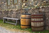 picture of acadian  - a bench and two barrels along side stone walls - JPG
