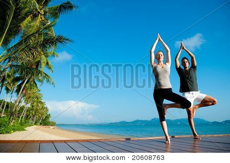 An attractive young woman and man doing yoga on a jetty with the blue ocean and another island behind them