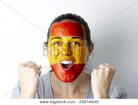Spanish fan screaming GOAL with hands up and painted flag on her face.