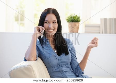 Pretty woman making phone call on couch in living room, smiling.?