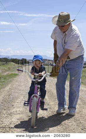 Grandfather Helping Boy Ride Bike