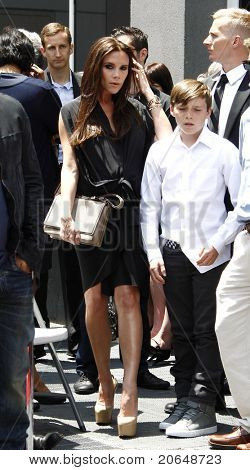 LOS ANGELES - MAY 23: Victoria Beckham, son Brooklyn at a ceremony where Simon Fuller receives a star on the Hollywood Walk of Fame in Los Angeles, California on May 23, 2011.