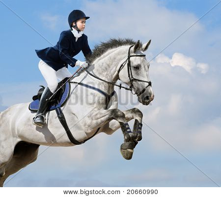 Young girl jumping with dapple-grey horse