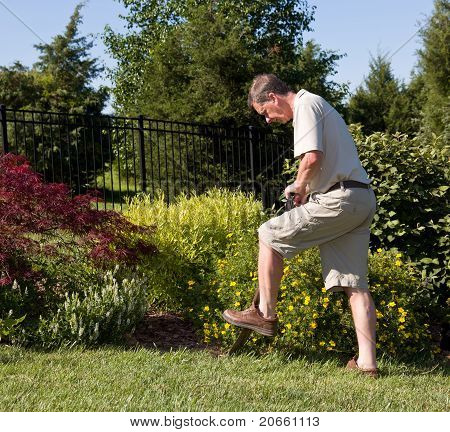 Senior Man Digging In Garden