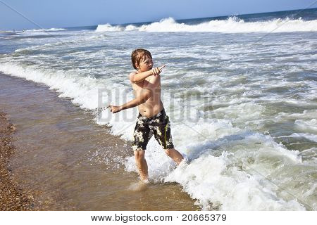 Boy In Motion At The Sea
