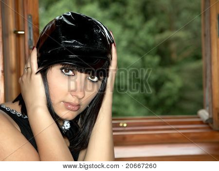 Girl In  Black Cap At  Window
