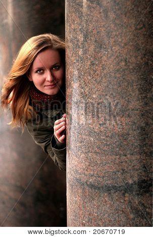 woman looking behind a wall