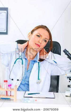 Mulher médico cansado sentado na mesa de escritório e massagear o pescoço