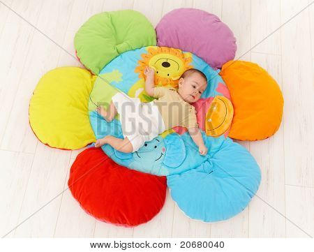 Baby lying on flower shape playmat, high angle.?
