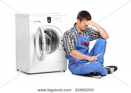 A desperate repairman posing next to a washing machine isolated on white background
