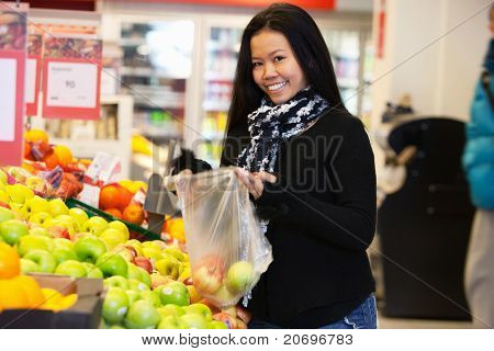 Portrait of a happy young woman buying apple in the supermarket