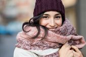 Closeup face of a young happy woman enjoying winter wearing scarf and cap. Smiling girl in a colorfu poster