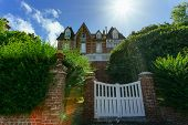 Country House With Green Fence And White Gate In Normandy, France On A Sunny Day With Sunbeam In Blu poster