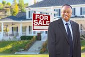African American Agent In Front of Beautiful Custom House and For Sale Real Estate Sign. poster