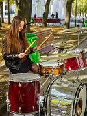 Festival music band in autumn park. Sad woman playing on percussion instruments in city park. Girl i poster