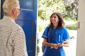 Senior man greeting female nurse making home visit poster