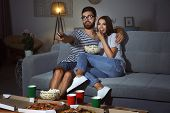 Young couple watching TV in evening at home poster