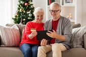 christmas, holidays and people concept - happy smiling senior couple with tablet pc computer and cre poster
