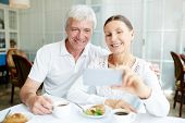 Affectionate senior spouses making selfie by cup of coffee in cafe poster