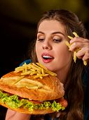 Woman eating french fries and hamburger. Student consume fast food. Girl bite of slice. Girl trying  poster